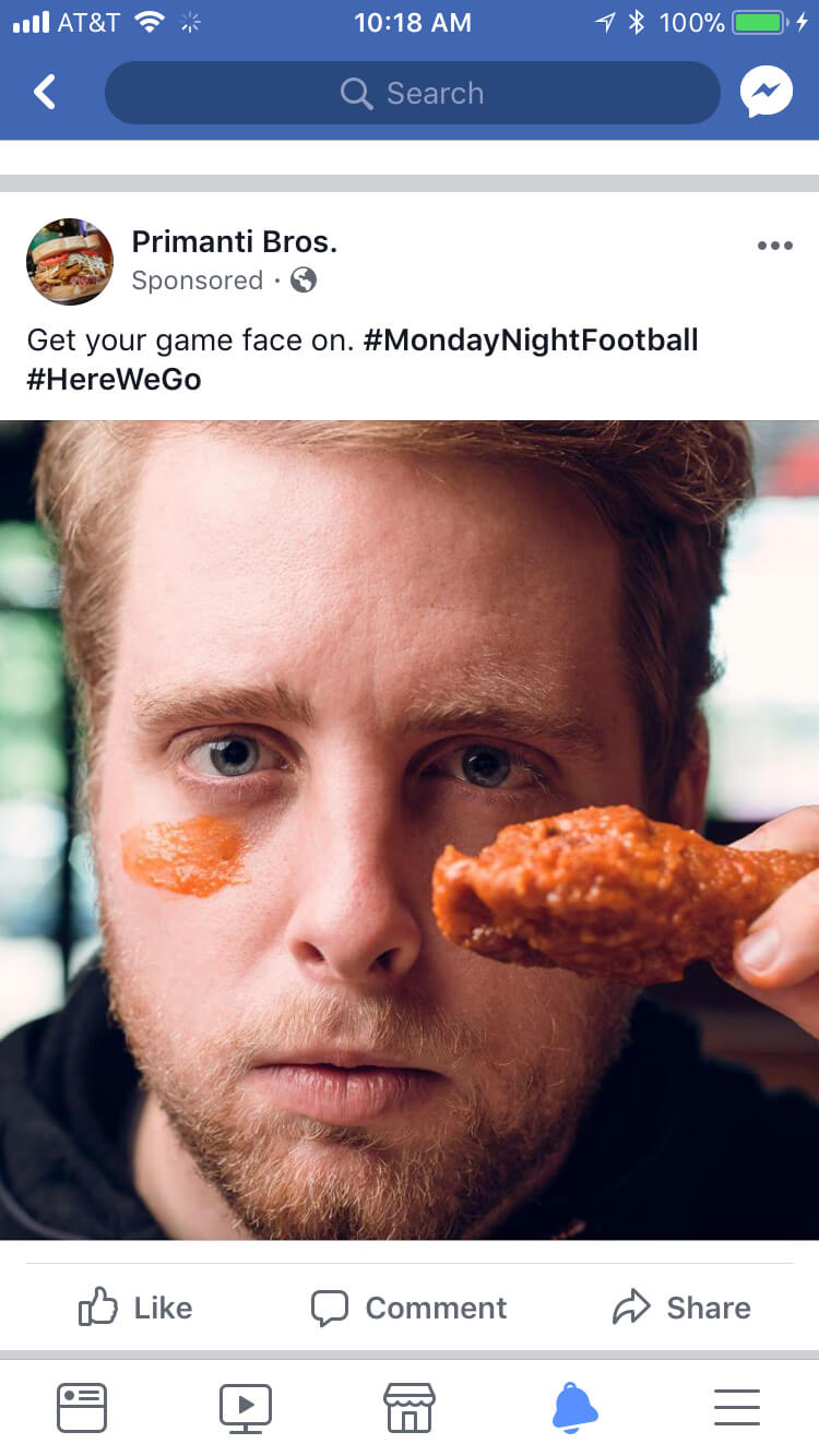 A social mock up of a close up shot with a man holding a chicken wing under one eye and wing sauce wiped under the other.