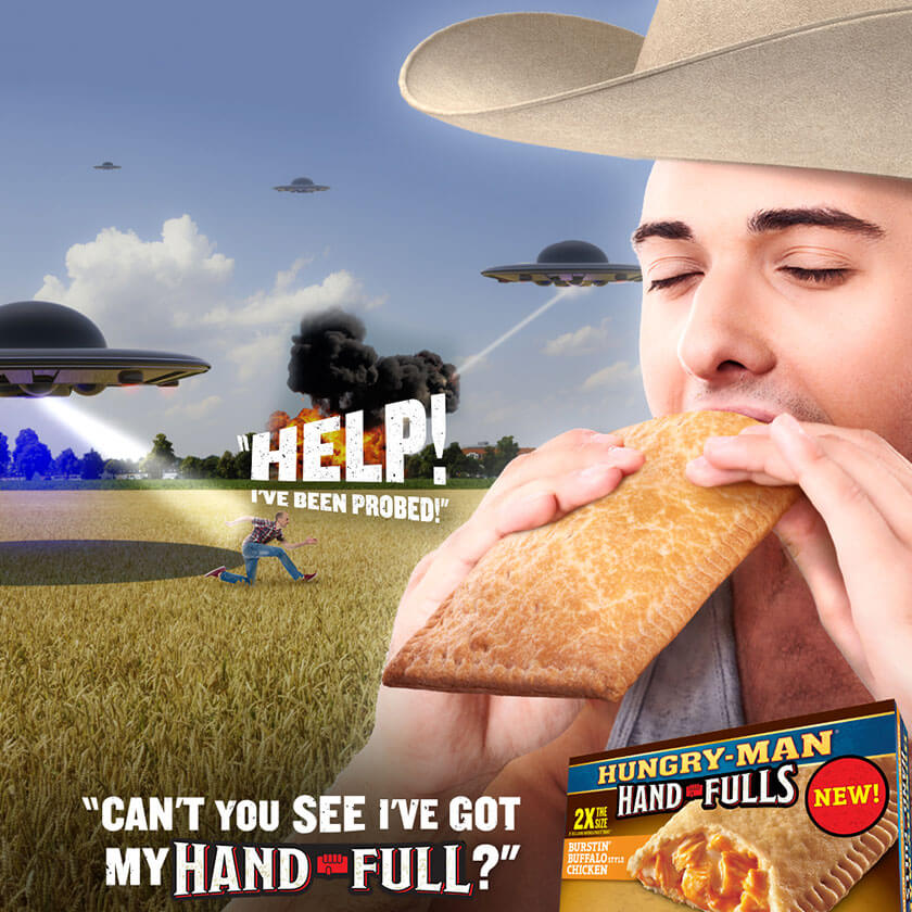 There is a man running through a feild being abducted by aliens. Text reads as if he is shouting: Help! I'm being probed! To the right of the image a man in a cowboy hat is eating a Hungry-Man Hand full and the text reads: Can't you see I've got my Hand Full!