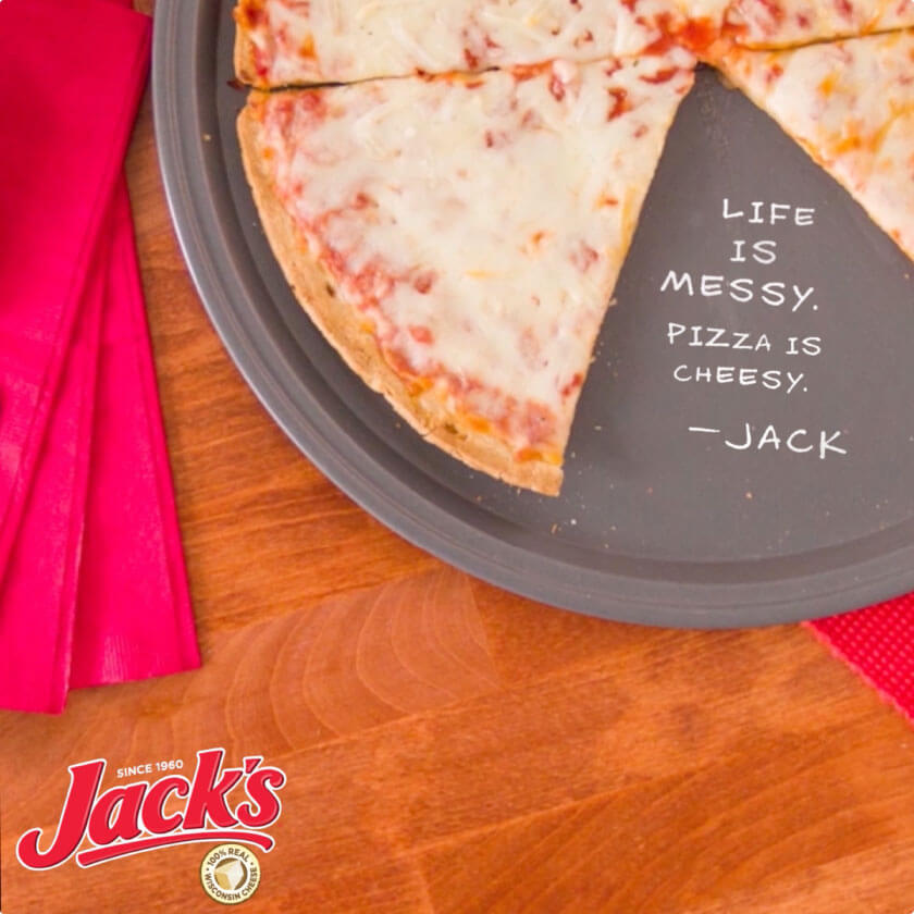 An overhead shot of pizza, with writing on the tray that reads: Life is messy. Pizza is cheezy. -Jack