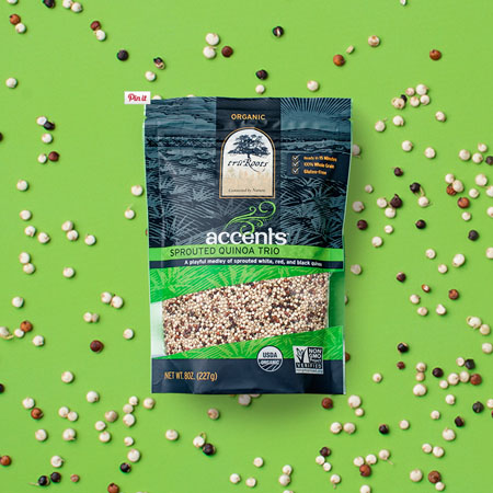 Tru Roots Accents Sprouted Quinoa Trio package shown on a background of green with quinoa scattered on it.
