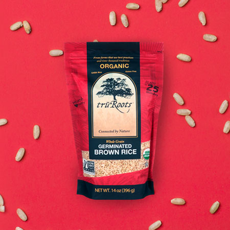 Tru Roots Organic Germinated Brown Rice package shown on a background of red with rice scattered on it.
