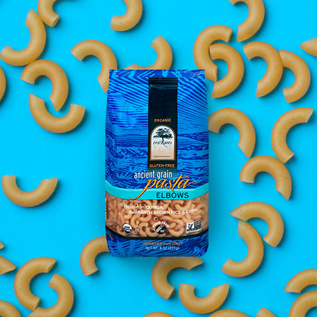 Tru Roots Ancient Grain Pasta package shown on a blue background with pasta elbows scattered on it.